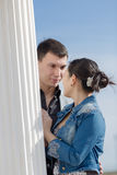 Asian girl and european guy standing face to face near of column Royalty Free Stock Image