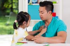 Asian girl examining her dad Royalty Free Stock Photo