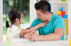 Asian girl examining her father Royalty Free Stock Photography