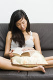 Asian girl falling asleep on sofa while reading Royalty Free Stock Images