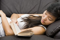 Asian girl falling asleep on sofa while reading Royalty Free Stock Photos