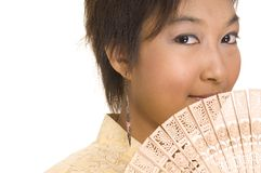 Asian Girl and Fan 2. A young asian woman holds a fan to her face Stock Photo