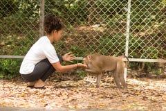 Free Asian Girl Feeding A Monkey Peanuts Stock Photo - 90728870