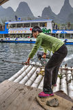 Asian girl ferryman crosses river on raft with motor, China. Royalty Free Stock Photos