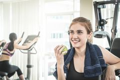 Asian girl in fitness eating green apple from working out break Royalty Free Stock Photo