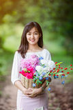 Asian girl with flower in the garden Royalty Free Stock Photos