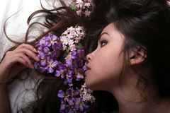 Asian girl with flowers. On her hair stock photos