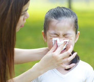 Asian girl with the flu. Cute little Asian girl with the flu, outdoor park Royalty Free Stock Image