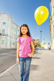 Asian girl with flying balloon standing on street Royalty Free Stock Photography