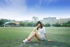 Asian girl in the football field of school. Sexy girl, waistline, jeans, free to unrestrained Royalty Free Stock Images