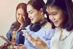 Asian girl and friend listening to music from black headphones and use laptop. Stock Photos