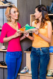 Asian girl friends shoe shopping in store Royalty Free Stock Image