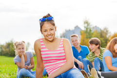 Asian girl and friends sitting together in park. On grass during wonderful sunny autumn day Stock Photography