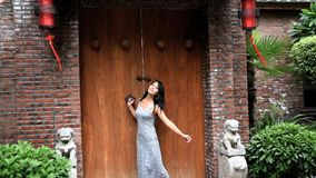 Asian girl in front of the ancient wooden door. Classical charm, red brick, dressed in long skirts, sweet smile stock video