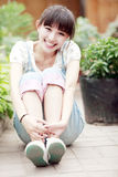 Asian girl in the garden. Asian smile girl sitting in the garden Stock Photography
