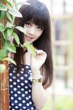 Asian girl in the garden. Charming Asian girl smiling in the garden Royalty Free Stock Photos