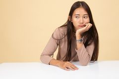 Asian girl is getting bore. On beige background stock photography