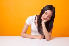 Asian girl is getting bore. Asian girl is getting bore on bright yellow background stock photography