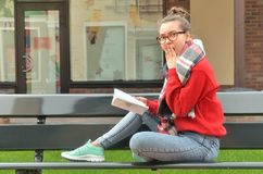Asian girl in glasses looking into the camera shocked. A beautiful Asian girl in glasses sits on a bench with a book. Looking into the camera shocked, covered Royalty Free Stock Photo