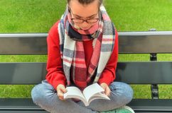 Asian girl in glasses reads a book. Asian girl in glasses sits on a bench, crosses her legs and reads a book. Around the lawn is a beautiful green grass. Top Royalty Free Stock Photo