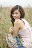 Asian girl among grass Stock Photo