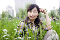 Asian girl in grassland. Asian girl sits  in grassland in summer Royalty Free Stock Photos