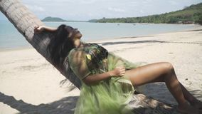 Asian girl in a green dress is lying on a palm tree trunk, resting, relaxing. Asian model girl in a green dress is lying on a palm tree trunk on the beach stock footage