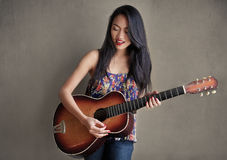 Asian girl with guitar Stock Images