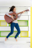 Asian girl with guitar jump in bedroom Royalty Free Stock Photography