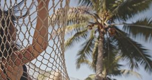 Asian girl on hammock by tropical beach next to the palm tree watching something. Exotic, relax, lifestyle, advertising