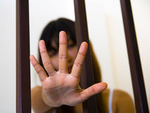 Asian Girl and hand behind bars Stock Photography