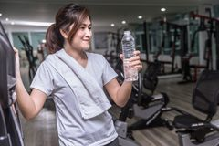 Asian girl hand hold drinking water bottle in sport club royalty free stock photography