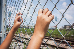 Asian girl hand hold jail Royalty Free Stock Images