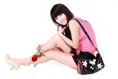 Asian girl with handbag. A beautiful Asian girl with handbag sits on white background.She holds a rose in the hand Royalty Free Stock Images