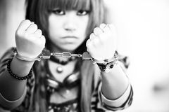 Asian girl with handcuffs. Young asian girl showing handcuffs on her wrists Royalty Free Stock Photos
