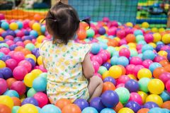 Asian girl have fun in ball pool. Rare shot of little girl having fun in ball pit with colorful balls. Child playing on indoor playground. Asian kid in ball pool royalty free stock image
