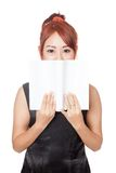 Asian girl hide her mouth with a book Royalty Free Stock Photos