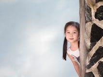 Asian girl hiding behind the wall Royalty Free Stock Photos