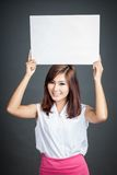 Asian girl hold blank sign over her head and smile Stock Images