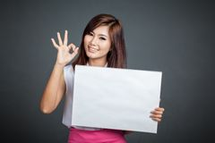 Asian girl hold blank sign show OK sign. On gray background Royalty Free Stock Photos