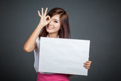 Asian girl hold blank sign show OK sign at her eye Stock Photo