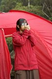 Asian girl hold cold hands to mouth. Asian girl wearing sunglasses holding cold hands to mouth with red tent outdoors Stock Photography