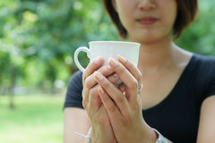 Asian girl hold a cup of coffee with her hand Royalty Free Stock Image