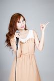 Asian girl hold microphone point to her left Royalty Free Stock Photography