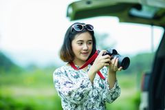 Asian girl holding a camera and checking photo Royalty Free Stock Image