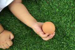 Asian girl holding egg with both her hands with care. Close up.like a take case something special all times stock image