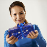 Asian girl holding gift box to the camera stock photography