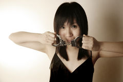 Asian girl holding handcuffs Royalty Free Stock Photo