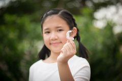 Asian girl holding hearing aid stock photography
