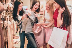 Asian girl is holding lace night shirt. It is very beautiful. Girls are looking at this shirt as well and touching it. They are amazed and excited royalty free stock photos